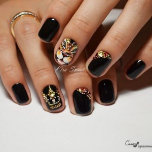 Black manicure with crown and tiger