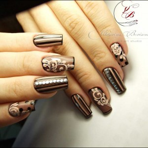 Brown biege and black manicure idea with striptd nail design and velvet roses